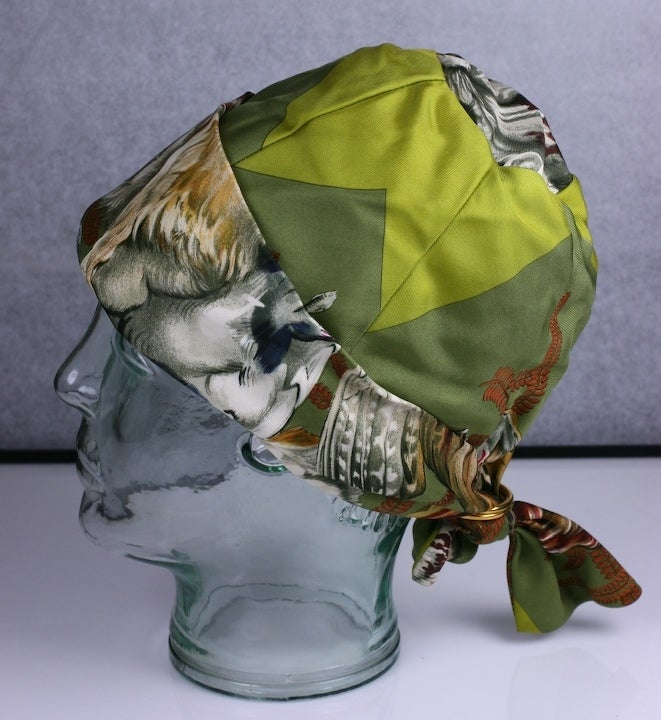 """Classic Hermes signature scarf print silk twill printed hat. Self ties with gilt metal """"D"""" rings. France 1970s. Circumference 20"""" with 1"""" elastic. 7"""" crown Excellent condition."""