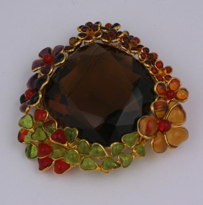 A large antique smokey quartz crystal from the 1930's is the focus of this brooch. Poured glass flowers of varying sizes and tones circle the crystal in autumnal tones.  Completely made by hand by our craftsmen in the French studios of Mark Walsh