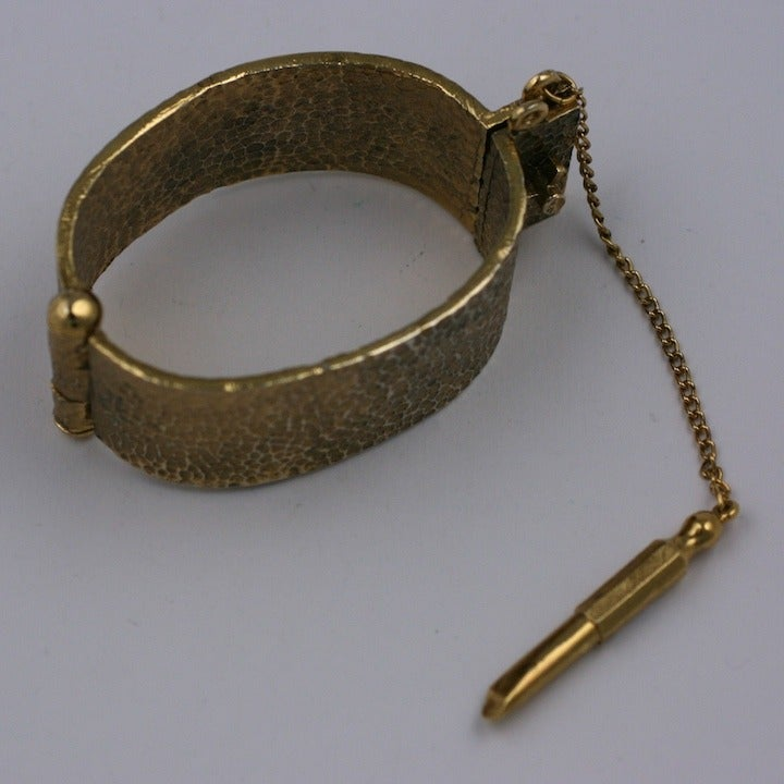 """Unique novelty bracelet of hammered gilt metal with attached """"key"""" to open cuff. Unusual and cool at the same time. Width 1 1/8""""  Interior 2 3/8"""" x 1 7/8"""". 1960's USA. Retains original label by Lisner, NY. Excellent condition."""