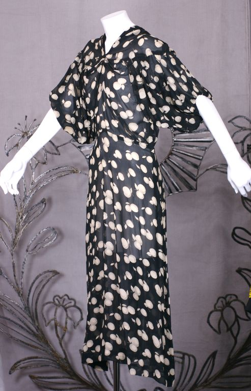 Silk chiffon dress from the 1930s with an unusual cut and modern presence. Oversized kimono sleeves fall from a yoke and are loosely gathered and float over the the dress in an unusual configuration. These large billowy sleeves are anchored over the