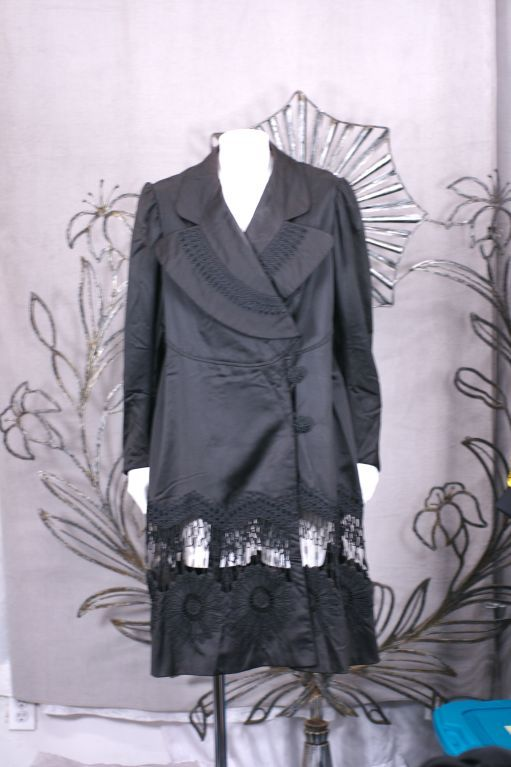 Unusual European walking coat from the late 19th/early 20th Century. Black cotton sateen is tailored with black passementerie and embroidery. A panel of passementerie openwork is attached below the hip line to reveal openwork attached to sunflower