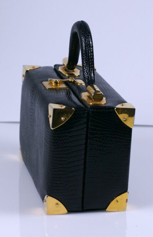 Charming miniature suitcase purse by Judith Leiber. Black snake with gilt mounts and charming shaped handle.Change purse as well. Retailed by Bonwit Teller.<br />
