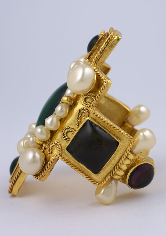Oversized Chanel cruciform cuff by maison Gripoix. Emerald, amythest and citrine pate de verre cabochons decorate all sides. Hand made faux pearls decorate this iconic baroque Chanel bracelet.