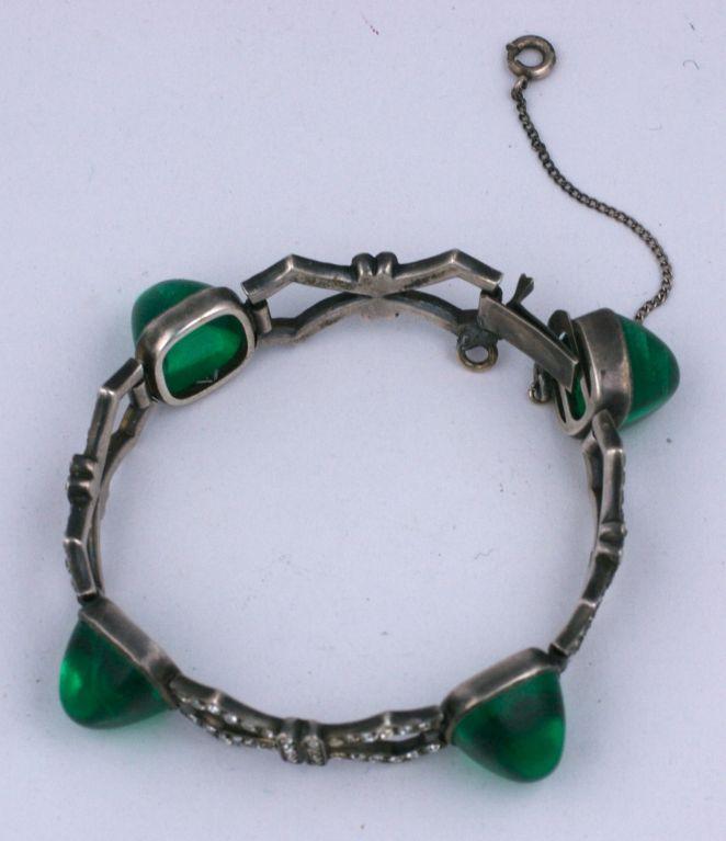 Elegant art deco paste bracelet set in sterling with large faux emerald bullet cab stones. Pierced articulted metalwork in art deco bow motifs.<br /> Excellent