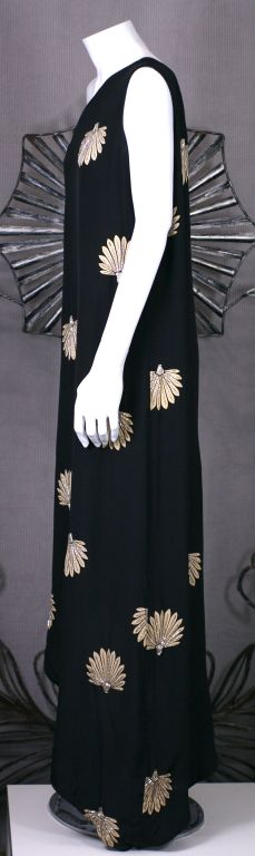 Elegant one shouldered gown by Adele Simpson of bias cut black silk crepe with beaded palm motifs. Side zip entry.<br />