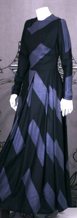 Unlabeled evening dress of the softest silk/cashmere twill. Graphic black diagonal stripe patterns on charcoal grey. Deep inverted pleats at the waist release to a very full skirt. Back zip entry. Undoubtedly a designer dress of the period. Size