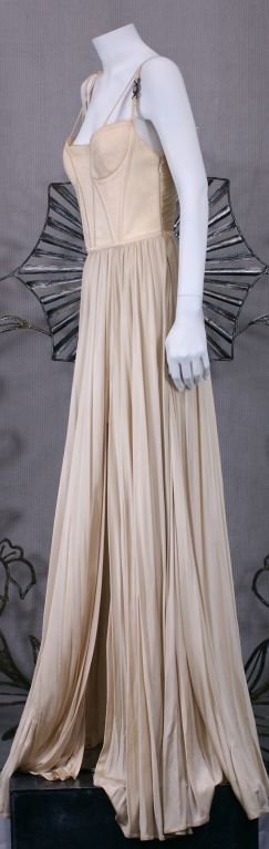 Versace Couture gown of ivory rayon matte jersey with a quilted and shirred bodice with a skirt of shirred floating panels. Shoulder straps are adorned with glass Medusa ornaments set into silvered metal buckles.