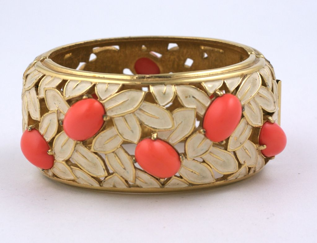 Lovely Jomaz cuff of pierced gilt metal with white enamel leaves and coral glass cabochons. Hinge side opening.<br /> Interior diameter 2.5 x 1.75