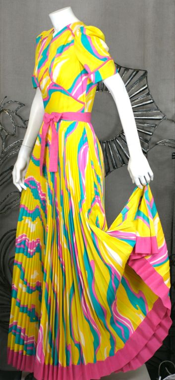 Sunburst pleated dress with a huge circular sweep skirt from the 1970s. Wonderful yellow pink and blue marbleized swirl print with contrast trim. Attached pink belt that wraps around twice.Back zip.<br /> Vintage Size 6 US.<br /> Excellent condition