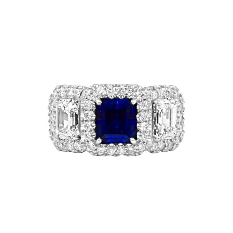 A royal blue three-carat rectangular emerald-cut Kashmir sapphire with two emerald-cut diamonds weighing a total of 2.17 carats (H-VS2), set in Platinum. The sapphire measures 6.44 x 5.89 x 6.99 mm and accompanies a gemological report from AGL