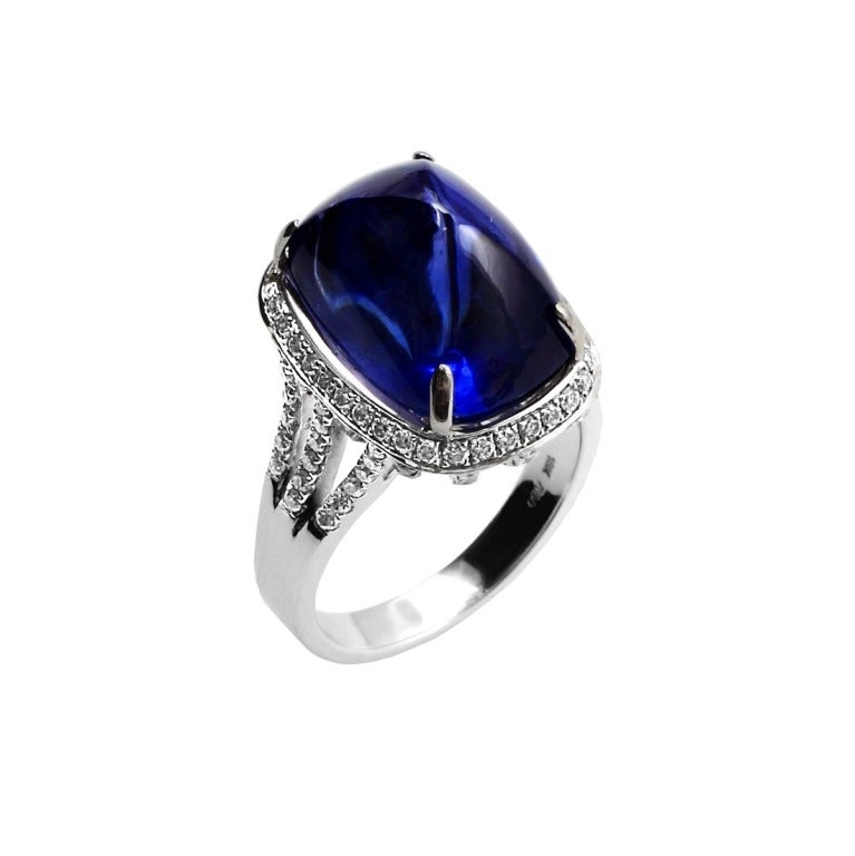 A 19.57 carat cushion-shape sugarlaof blue sapphire cabochon with diamonds, set in 18kt white gold. The sapphire accompanies a gemological report from GIA & GRS stating the country of origin as Ceylon (Sri Lanka) with No Heat Enhancement. Ring Size: