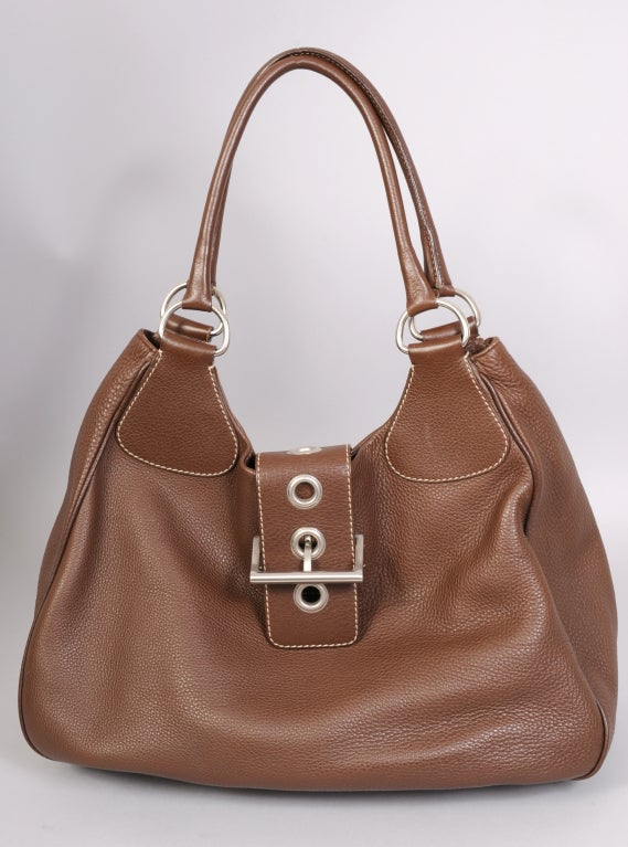 Chocolate brown textured leather is accented with white stitching and silver toned metal hardware in this Prada day bag. The generous straps easily slide over your shoulder. The buckle and eyelets allow you to put a few extra things inside. The