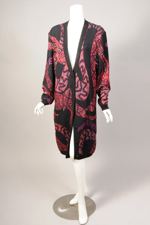 This Missoni sweater coat is not for the faint of heart! The multi color design on a black background is a swirling stylized snake pattern. The sweater buttons all the way down the front and there are two large pockets concealed in the pattern. It