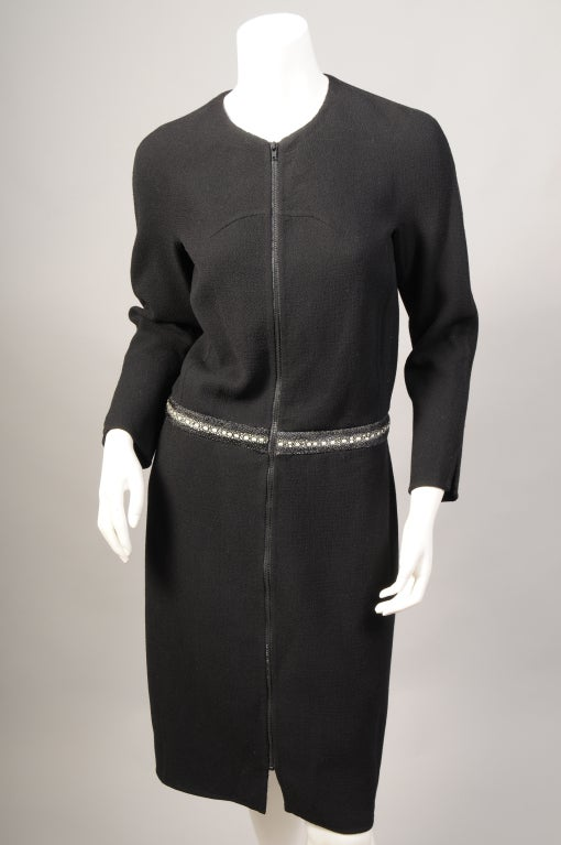 Ralph Rucci is known for his elegant designs, exquisite construction, and juxtaposition of fabrics. This clean lined black wool crepe day into evening dress is a perfect example. The collarless dress has long sleeves and a zipper at the center