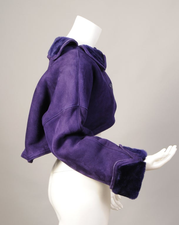 Regal purple suede and deep purple shearling make for a smashing bolero jacket designed by Alber Elbaz while he was working at Geoffrey Beene. The striking jacket has two purple leather buttons and a shearling collar and cuffs. It is fully lined in