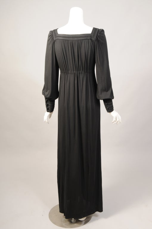 Rich black silk jersey is trimmed with bands of soutache braid and cord on the square neckline and on the deep buttoned cuffs of this dress from the Rive Gauche line. A slightly Empire waistline is emphasized with a tasseled braid belt that ties at