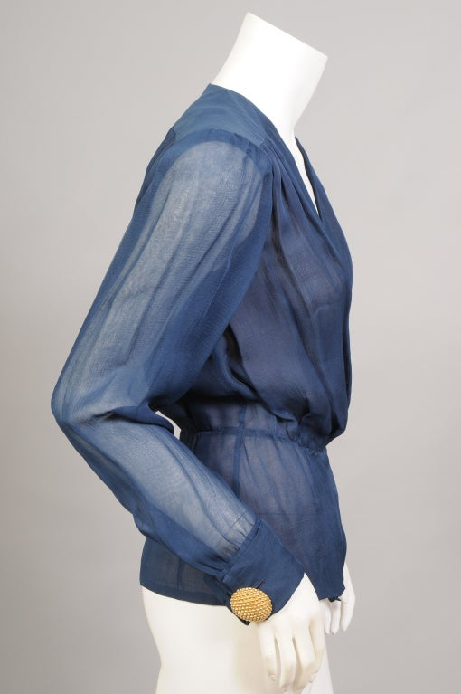 Deep blue silk georgette is lined with a mocha silk georgette in this elegant and sexy blouse from Yves Saint Laurent Haute Couture, from the 1970's. The blouse has long sleeves with French cuffs and oversized YSL cufflinks. One side is a stylized