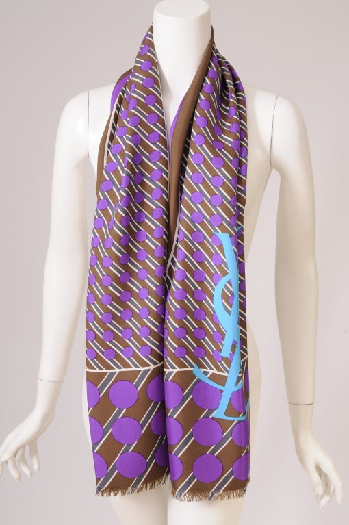 A strikingly graphic silk scarf from Yves Saint Laurent incorporates a bold turquoise logo on a scarf printed with purple polka dots and cream and grey dashes on a brown background. It is in excellent condition.  Measurements; Length 66