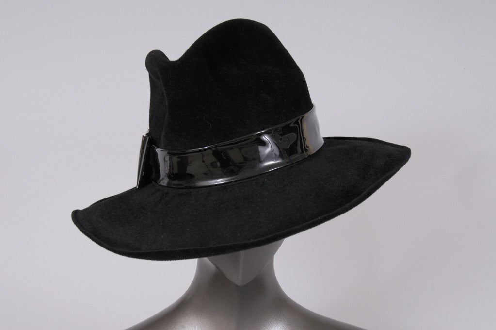 A very chic fedora designed by the famous Italian hat maker Borsalino is unusual because it is made from angora and trimmed with a black patent leather hat band. It is in excellent condition.
