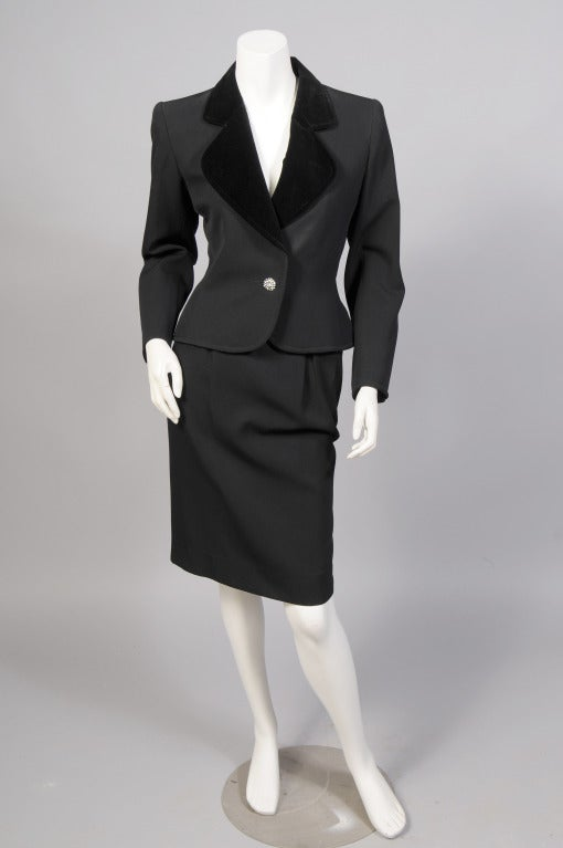 Yves Saint Laurent is famous for his tuxedo look for women, Le Smoking. This elegant evening suit is another version of that look. The black wool jacket is accented with a black velvet lapel and cuffs. There is a single jeweled button at the center