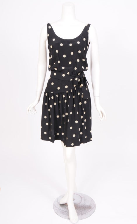 A black silk background with big creamy white polka dots from Martha, Palm Beach is a charming vacation dress. The sleeveless top blouses slightly over the fitted hip panels. The skirt is softly gathered and there is a matching tie belt. The dress