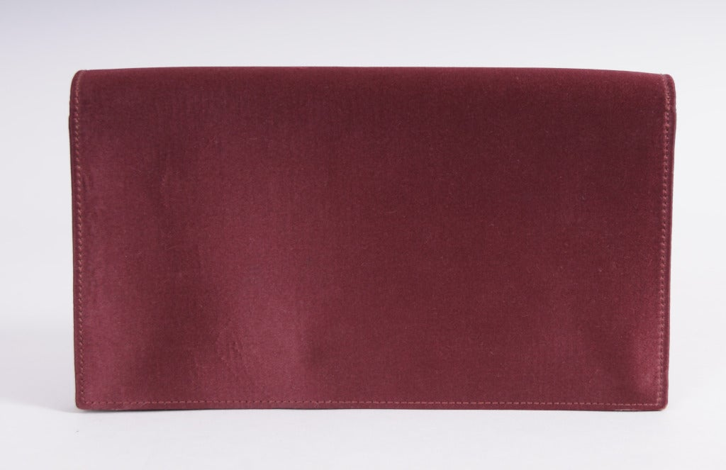 A rich burgundy silk satin covers this leather lined evening bag from Hermes, Paris. Inside there is a zippered compartment and an open slip pocket as well as a larger slip pocket just below the Hermes logo stamp. The optional shoulder strap is no