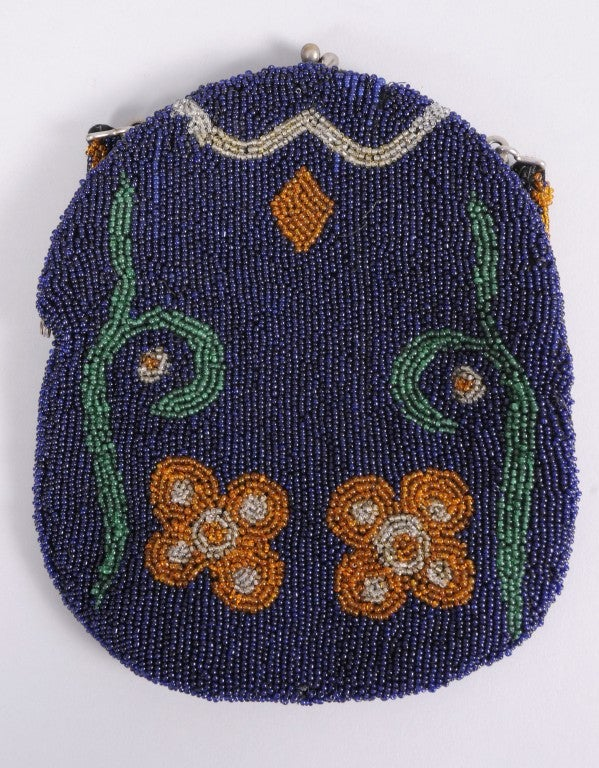 From a Beverly Hills collector, a deep navy blue background shows off the gold flowers and green leafy branches on this beaded bag. The beaded handle incorporates all of these colors. The bag has a kiss-lock closure and it is fully lined in faille.