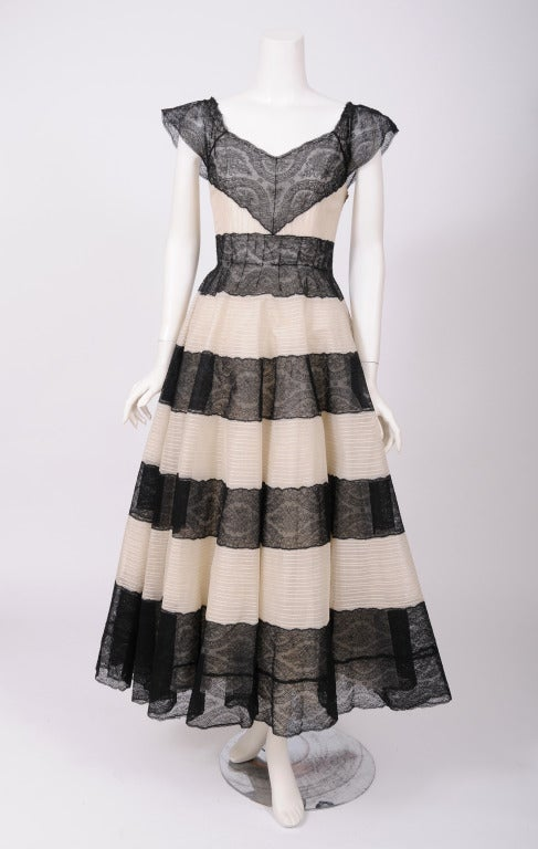 Black lace and pin tucked cream colored tulle alternate in wide bands to create a visually striking dress from the Couture House of Jean Patou. Designed in the late 1930's or early 1940's this dress has a boned bodice and it is fully lined,