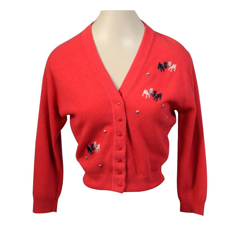 Vintage Pringle cashmere sweaters with hand inlaid Intarsia designs are rare, so to find one with such a charming and witty design is a rare treat! This coral/red  V-necked cardigan sweater is embellished with pairs of Scotties and Westies playing