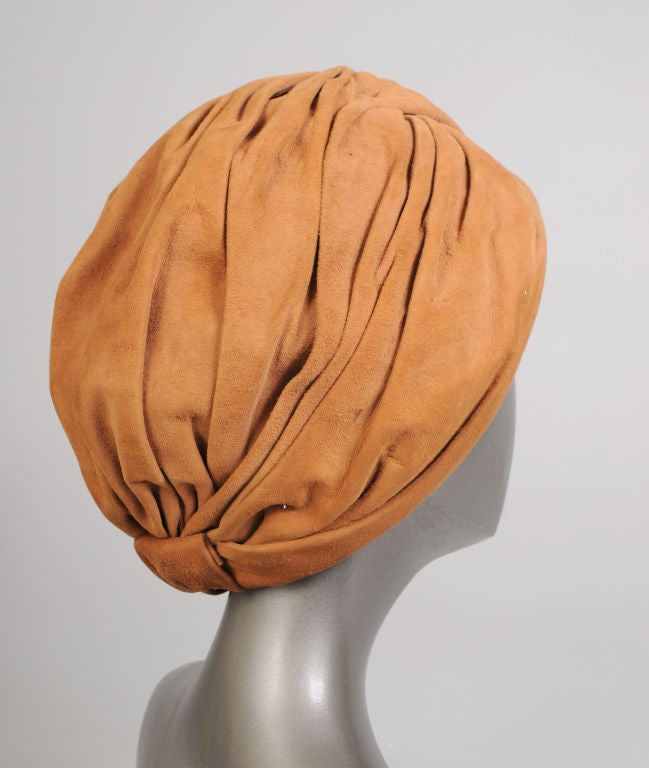 "Luscious caramel colored suede is draped from a central point atop the head to create a very glamourous ""old Hollywood"" style turban.<br />