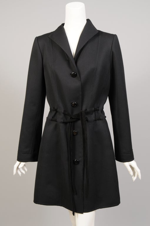 Italian designer Raffaella Curiel designed this chic, lightweight and unlined  black wool coat. It is perfect now and right through spring. The coat has two belts, leather or suede, that lace through at the waistline and ties at the front. It is
