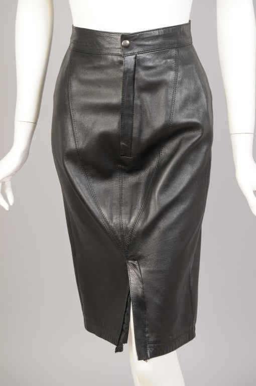 Azzedine Alaia uses soft black leather for this form fitting skirt with double zippers. The skirt has a narrow waistband with a snap above the zipper fly. There is another zipper at the hemline of the skirt, opening up to show more leg. Two elastic