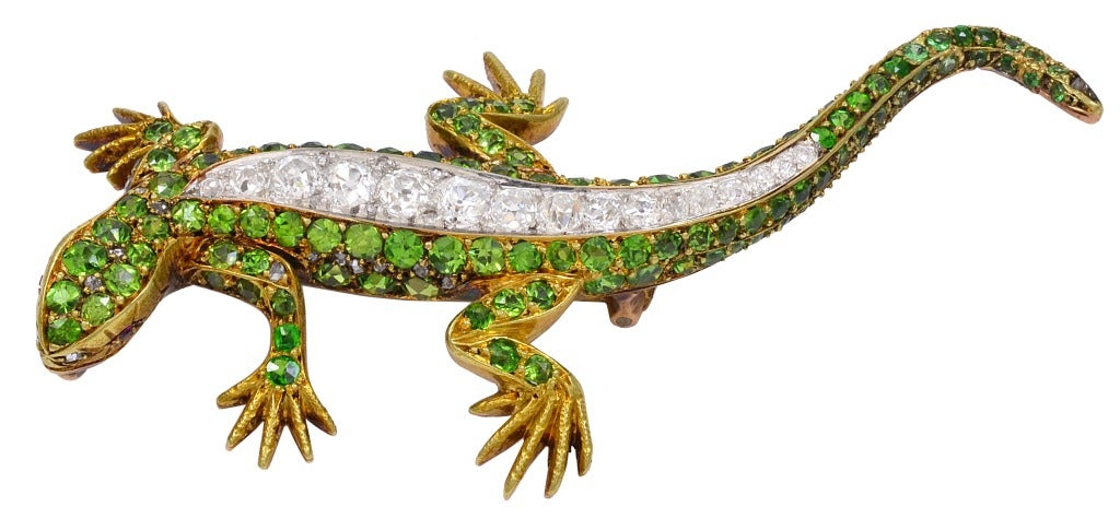 A stunning demantoid garnet and diamond 18k yellow gold lizard brooch.  There is approximately .63cts total in diamonds.  While garnets have been known since ancient times, the demantoid variety was not discovered until 1868 in Russia's western