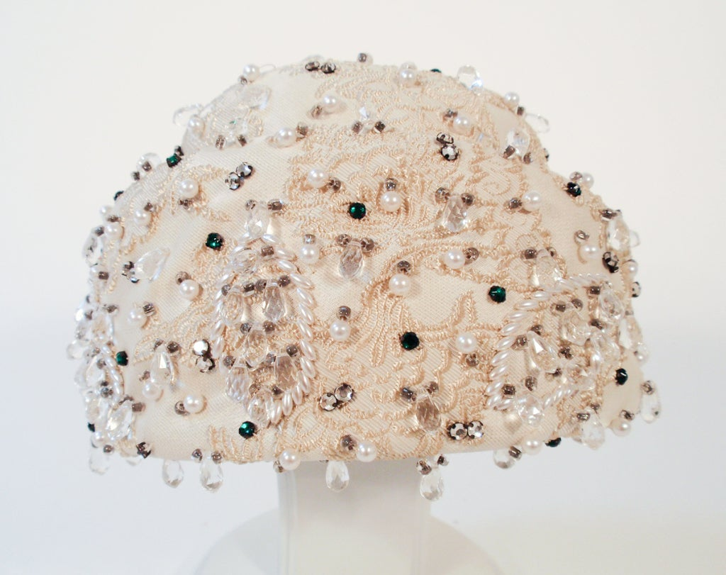 "This is a lovely vintage hat from Christian Dior. tag reads ""Christian Dior Chapeaux"". It is made of an ivory colored brocade fabric, embellished with lots of pearls, crystals, and green rhinestones.