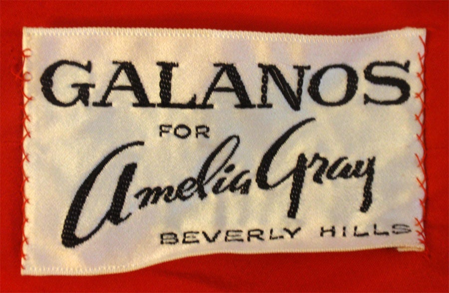 This is a red chiffon cocktail dress by Galanos for Amelia Gray, from the 1960's. The dress has white stripes on the skirt with two layers of chiffon and a silk slip. There are white plastic buttons down the back bodice, and a fitted waist with