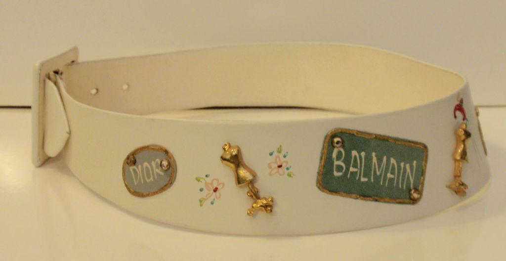 This is an adorable novelty belt that was made for Saks Fifth Avenue by Calderon. It is made of white leather and has designer names painted on it and metal dress form  and rhinestone embellishments.  Measurements:  Length: 27