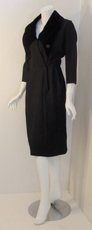 This is a long sleeve black dress with a velvet collar by Christian Dior, from the 1960's. It has two large black buttons on the collar, snap closures in the front, pleats at the waist, and a slit in the back.