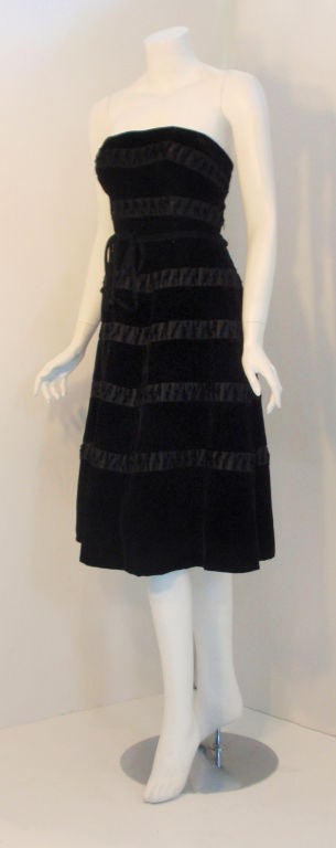 This is a strapless black velvet cocktail dress by Harvey Berin, from the 1960's. It has a high waist with a velvet tie belt, rows of black silk ribbon with small bows, six black silk bows down the back, with a back zipper.