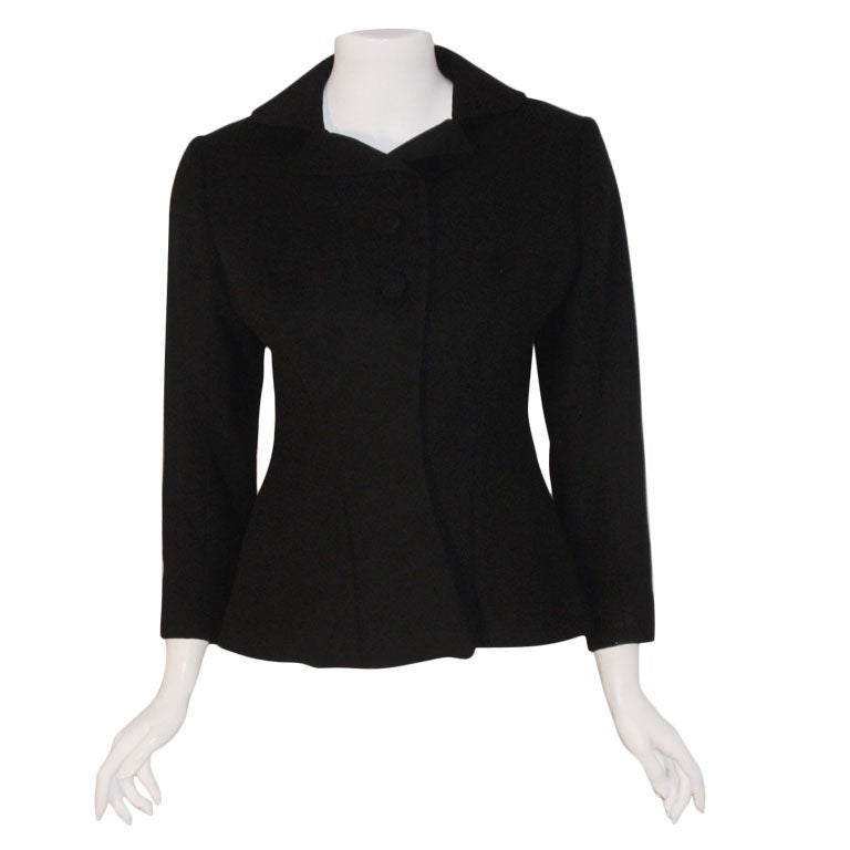 This is a very rare black wool blazer by Charles James, from the 1940's. The blazer has two buttons at the bust, a row of hidden snaps down the front, and beautiful design detail.  Measurements:  Length: 22 1/2