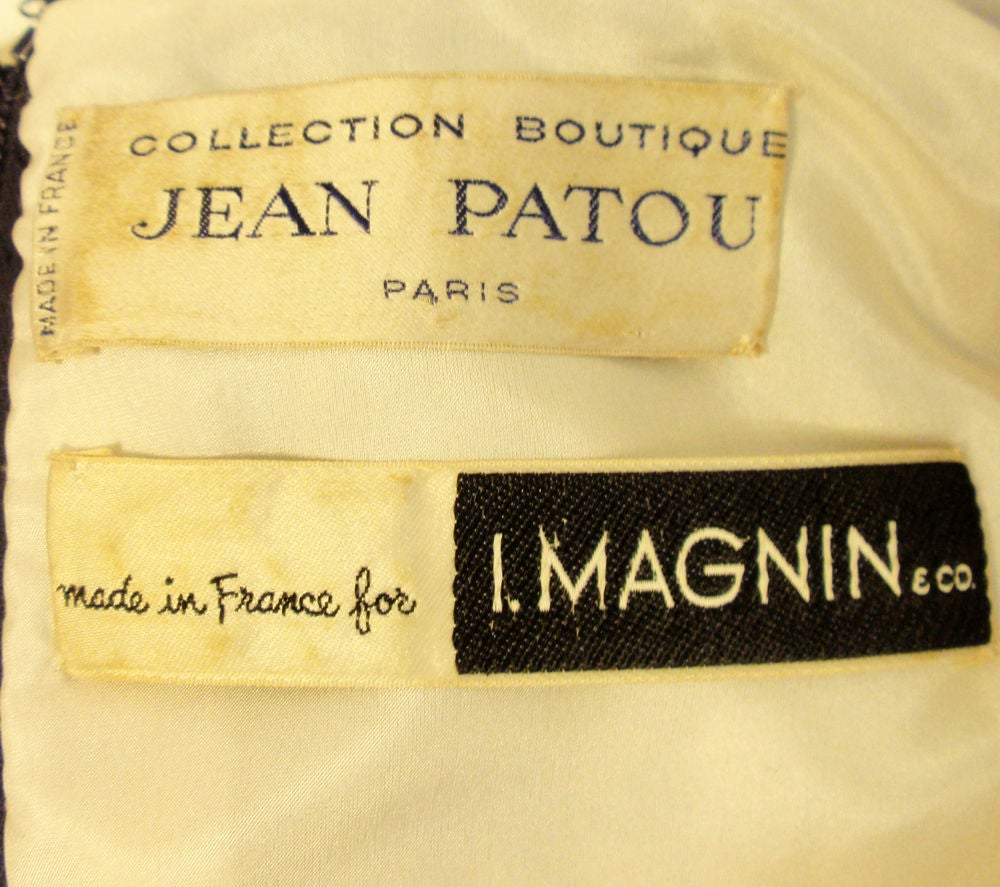 This is a vintage collectible dress from Jean Patou. It was made in France for I. Magnin. It is made of a navy blue and white wool houndstooth checked pattern fabric, with navy grosgrain detail and fully lined in a white silk. There are 2 patch