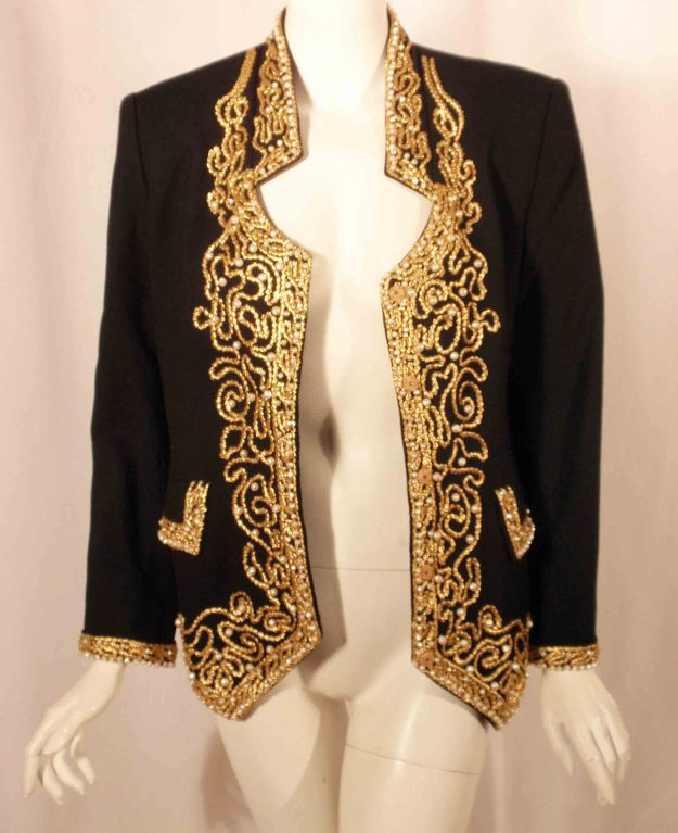 Fabulous black wool jacket with gold ribbon and pearl detail by Adolfo, New York, from the 1980's. The jacket is lined in black silk with hidden snaps down the front, and two flap pockets.  Shoulder to shoulder:16.5