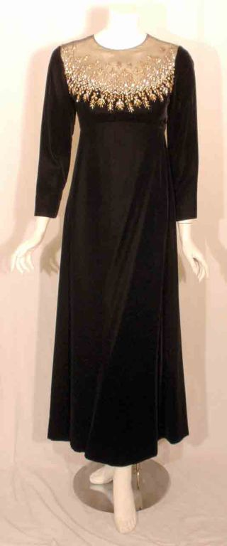 This is a long black velvet evening gown by Malcolm Starr, from the 1980's. The gown has beading and rhinestones around the front and back neckline, empire waist, black lining, and a zipper up the back.  Measurements:  Size# 8  Length
