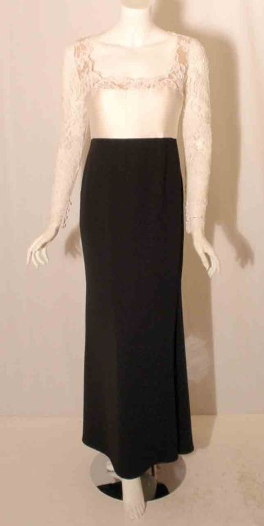 This is a white and black gown by Badgley Mischka. The gown has a lace bodice with a satin panel, scoop neckline, empire waist, and bridal buttons up the back with a zipper.  Measurements:  Length (Shoulder to hem): 55 1/2'  Sleeve: