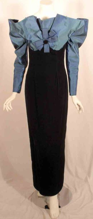 """Avant Garde"" gown by Victor Costa, from the 1980's. The gown falls off the shoulder with a long sleeve, bow in the center, a taffeta bodice, and a velvet skirt.