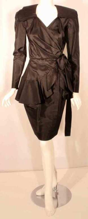 This is a sleek black silk wrap dress by Adolfo, from the 1980's. The dress has long fitted sleeves with zippers at the cuffs, a collar, wraps at the waist with a belt, shoulder pads, and a ruffles at the hip.  Measurements:  Shoulder to