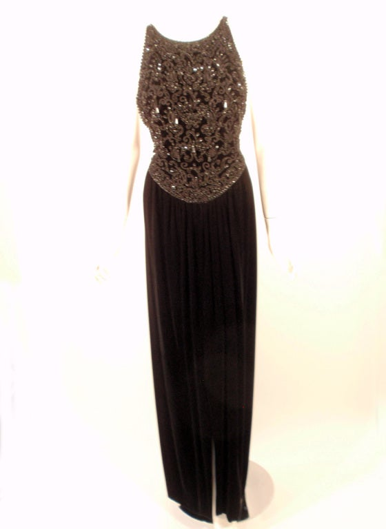 This is a sexy evening gown from Oscar de la Renta. It is made of black velvet and has a fully beaded bodice. It is a halter style top, that crosses in the back. The skirt is slit up the front. Lined.  Size 6 US  Measurements:  Bust: