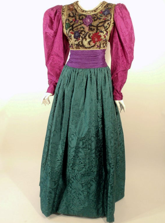 This is a fabulous evening gown made by Oscar de la Renta, from the 1980's. It is made from fushia pink, purple, and forest green jewel tone jacquard satin with a multi-color beaded bodice. The sleeves have some slight shoulder pads for volume,