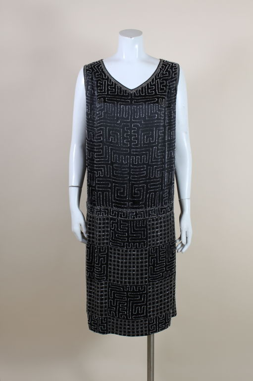 This lovely, Art-Deco era piece is made from a lightweight, black silk chiffon hand embroidered with white glass beads in a repeating geometric grid pattern. Drop waist is accented with a contrasting panel of beading.