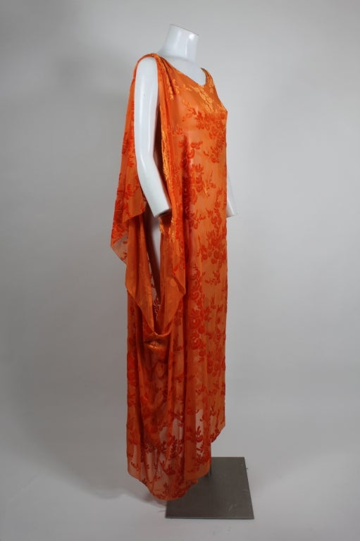 Gorgeous 1920s silk chiffon dress with floral burnout velvet accents. A vibrant orange and asymmetrical draping on the right side give this dress a modern and versatile feel. Snaps on right shoulder.
