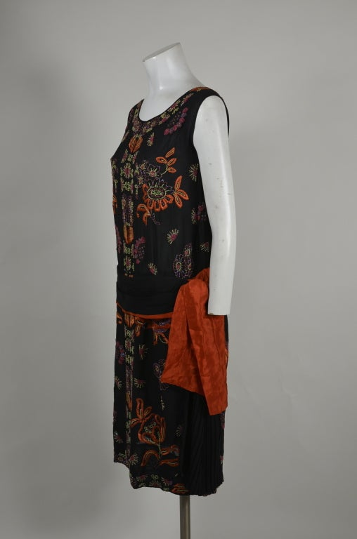 Stunning cocktail dress. Black silk chiffon. Beaded and embroidered in a symmetrical botanical motif in a palette of orange, purple, and green. Pleated sash with side swag at classic 20s drop-waist.
